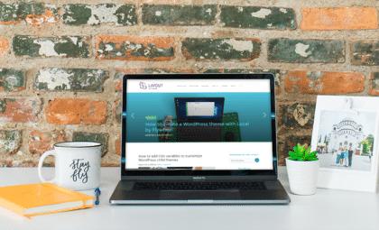 inspiring wordpress website designs blog on laptop with desk scene on brick wall