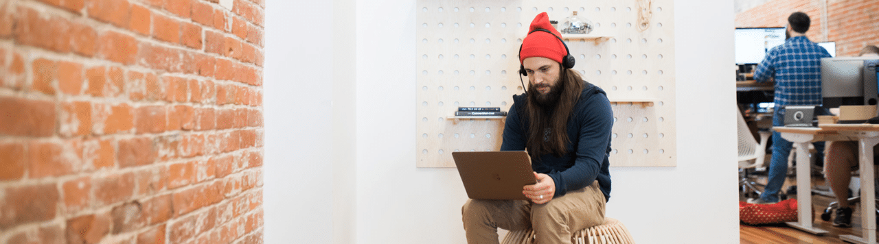 man on laptop next to plant wall with bricks using facebook advertising tools to increase sales
