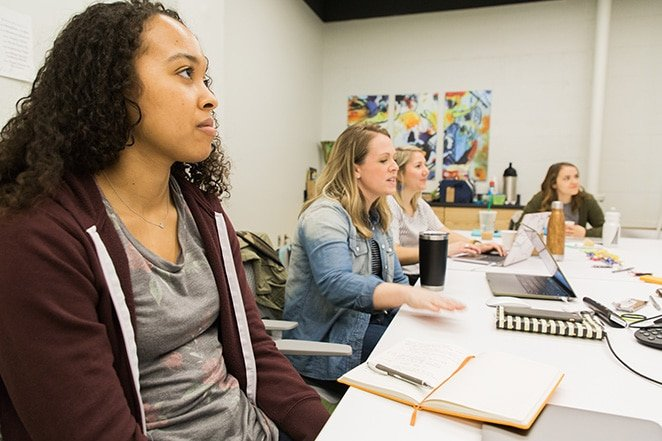 layout by flywheel develop marketing strategy for design agency how to women sitting at table with notebooks and laptops in brainstorm
