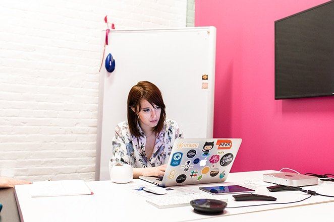 layout by flywheel how to create custom post template wordpress woman sitting at desk with laptop covered in stickers